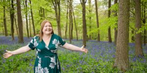 Hannah with outstretched arms in blue bell wood