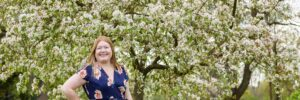Hannah in front of apple blossom tree