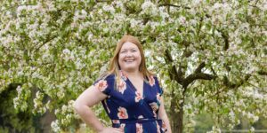 Hannah in front of Apple tree in blossom.